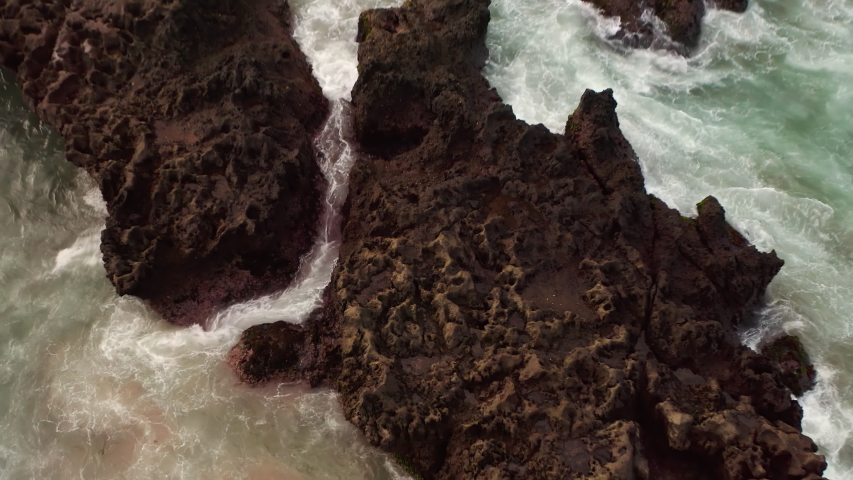 Aerial top view of waves break on rocks in a blue ocean. Sea waves on beautiful beach aerial view drone 4k shot. Bird's eye view of ocean waves crashing against an empty stone rock cliff from above. | Shutterstock HD Video #1053462617