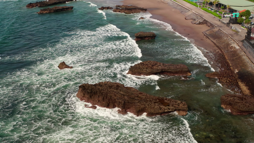 Aerial top view of waves break on rocks in a blue ocean. Sea waves on beautiful beach aerial view drone 4k shot. Bird's eye view of ocean waves crashing against an empty stone rock cliff from above. | Shutterstock HD Video #1053462629