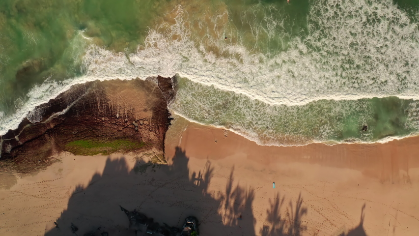Aerial view from above on a tropical island and ocean waves crashing and foaming against sand beach. Bird's eye aerial shot of golden beach meeting deep blue ocean water. Tourism concept after covid. | Shutterstock HD Video #1053462635