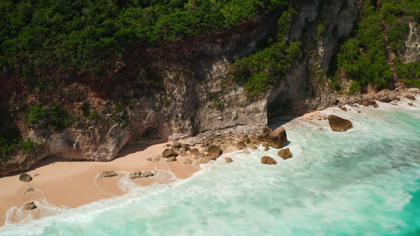 Aerial top view of ocean blue waves break on a beach. Sea waves and beautiful sand beach aerial view drone shot. Bird's eye view of ocean waves crashing against an empty sand beach from above. | Shutterstock HD Video #1053462641