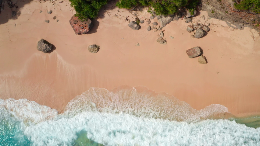 Aerial top view of ocean blue waves break on a beach. Sea waves and beautiful sand beach aerial view drone shot. Bird's eye view of ocean waves crashing against an empty sand beach from above. | Shutterstock HD Video #1053462647