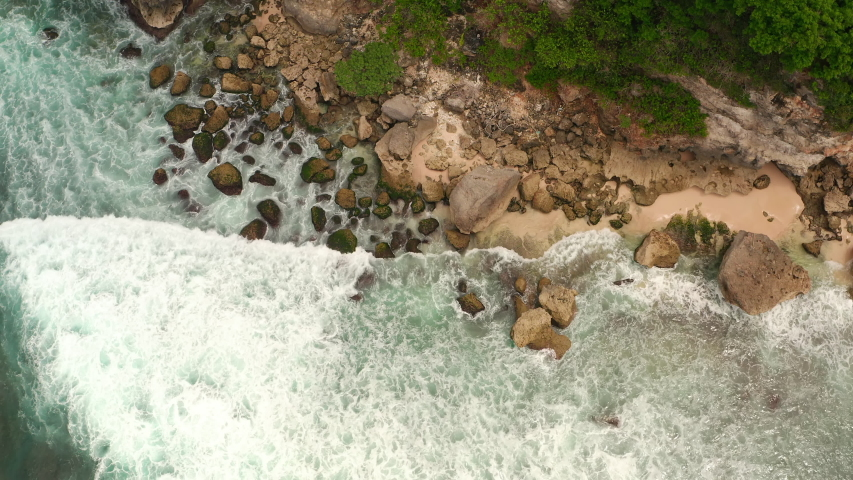 Aerial top view of waves break on rocks in a blue ocean. Sea waves on beautiful beach aerial view drone 4k shot. Bird's eye view of ocean waves crashing against an empty stone rock cliff from above. | Shutterstock HD Video #1053462650