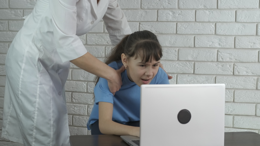 Child time by a computer. A teen with interest sits and plays on a notebook. Doctor pulling a child out from behind a computer. | Shutterstock HD Video #1053464264
