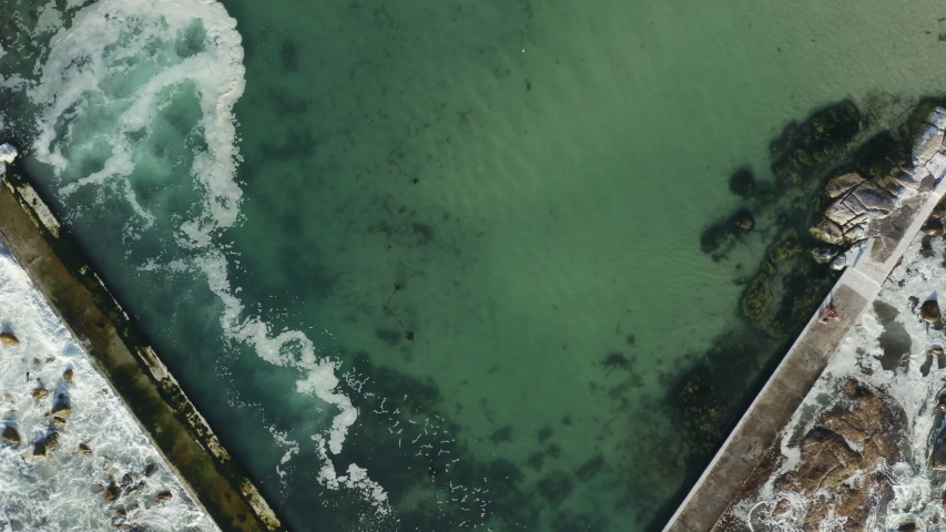 Top down aerial view of a sea defense wall protecting a sandy beach in Camps Bay, Cape Town from the power of oncoming waves.