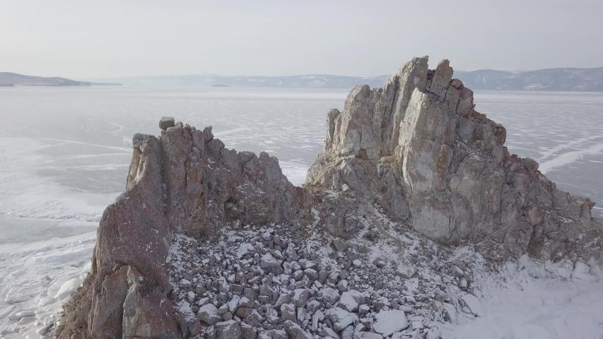 Aerial shot of Shamanka rock on Olkhon island in winter. Frozen lake Baikal in daylight, Siberia, Russia. Drone flies above mountain between rocks. Natural  snowy landscape.