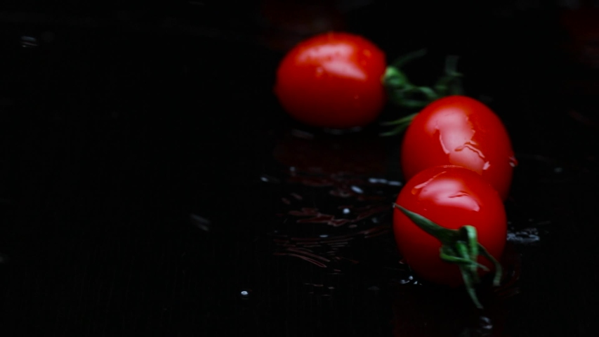 Red cherry tomatoes fall on the black wet table. The footage was shot in slow motion | Shutterstock HD Video #1053466655