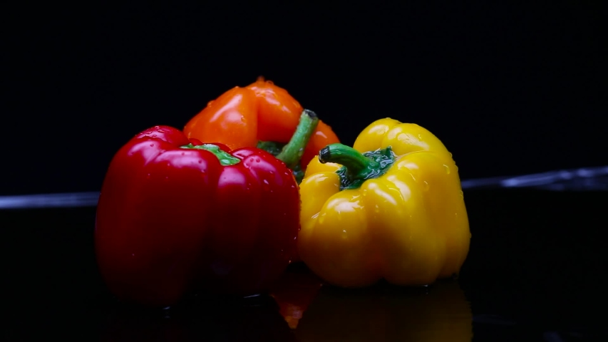 Water is poured on a fresh large and colorful bell pepper. The footage was shot in slow motion on a black background | Shutterstock HD Video #1053466661