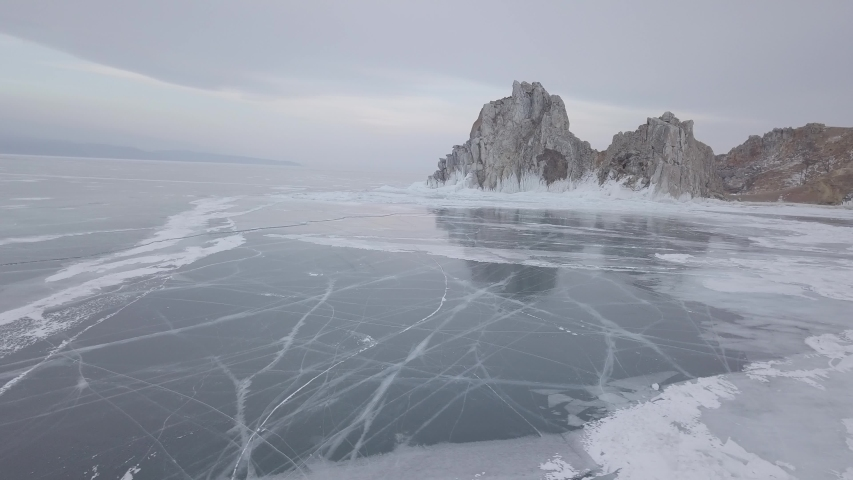 Aerial footage of Shamanka rock (mountain) ands Cape Burkhan on frozen Baikal lake on Olkhon island in winter. Russia. Beautiful snowy patterns on ice. Natural landscape of Siberia. Drone flies around