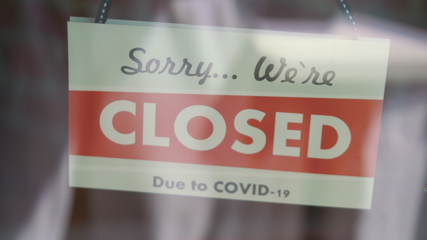 Closed sign hanging on the glass during pandemic time in 4K Slow motion 60fps | Shutterstock HD Video #1053468911