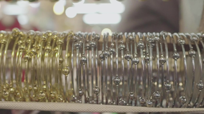 Closeup shot of jewelry bangles.Gold and silver jewelry. | Shutterstock HD Video #1053469490
