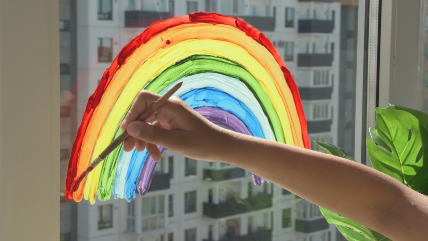 Girl painting rainbow on window during quarantine at home.