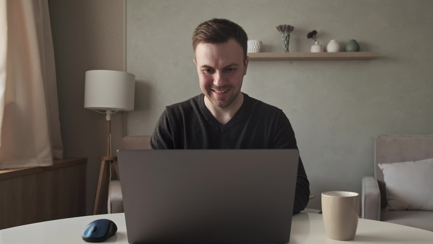 Young man opens laptop and starts working at living room. Student studying online using laptop. Handsome man at remote work because of quarantine. 4K, UHD | Shutterstock HD Video #1053471710