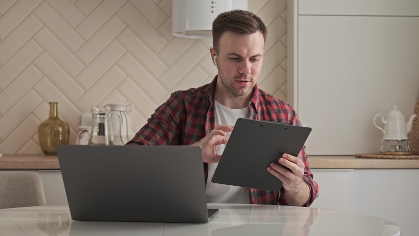 Young man working at home. Quarantine remote work concept. Freelancer working on laptop at kitchen. Video call. 4K, UHD | Shutterstock HD Video #1053471722