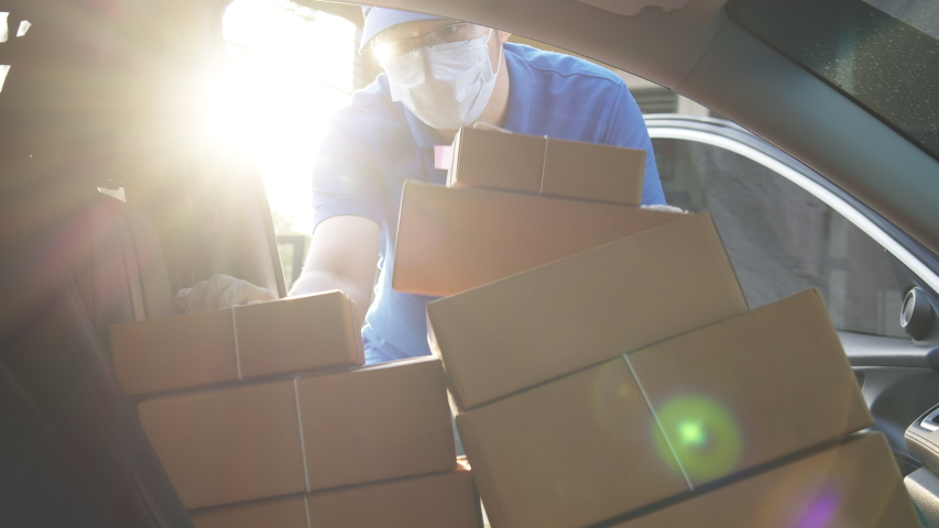 Asian volunteer delivery man or freelance re-arrange and deliver parcel paper box package in car at front house. Man in uniform, face mask and hand gloves for prevention coronavirus pandemic