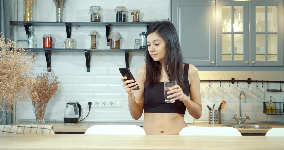Portrait of a young woman drinking water and watching a news feed on social networks on a smartphone in the kitchen in the morning. | Shutterstock HD Video #1053473186