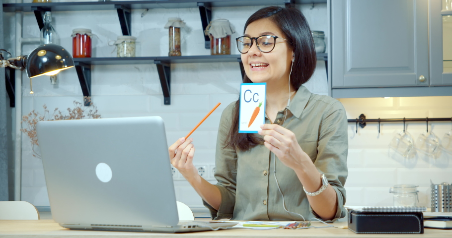 Young woman teacher showing pictures with the alphabet, learning letters and words, studying with a child or kids online using a laptop at home. Preschool Online Education Concept. | Shutterstock HD Video #1053475022