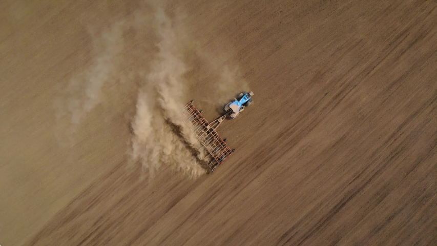 Aerial view tractor plowing fields and preparing arable area for sowing crops in food industry. Spring agronomic activity on agricultural land | Shutterstock HD Video #1053476012