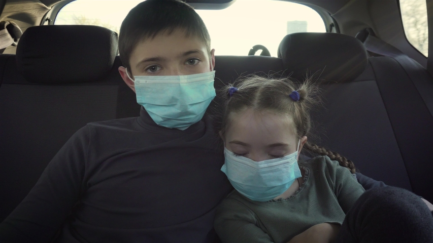 Close up kids boy and sleepy girl in medical mask looks sadly at camera on back seat of driving car during worldwide virus epidemic. Stop COVID-19 infection and pandemic