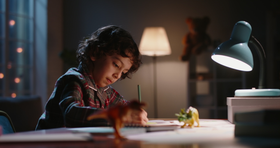 Funny little asian kid drawing at home. Boy with curly hair using his imagination, creating art in evening at home, dreaming of becoming artist - childhood dream, hobby concept 4k footage