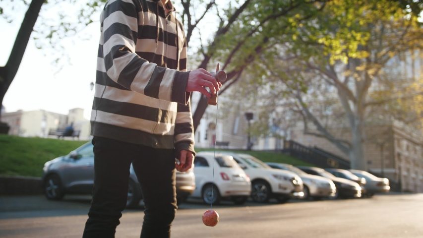 Young teenage boy playing kendama outside in city during beautiful sunset, slow motion | Shutterstock HD Video #1053478097