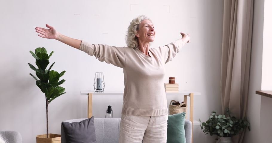 Excited middle aged 70s beautiful healthy woman standing with outstretched arms, feeling emotional indoors. Happy elderly mature grandmother welcoming new day, doing morning stretching exercises. Royalty-Free Stock Footage #1053479321