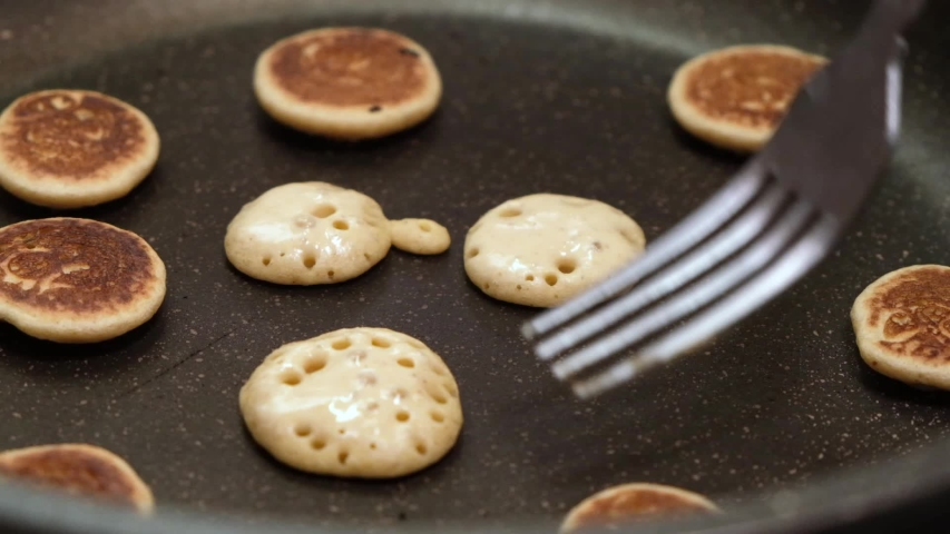 Process of cooking baked tiny pancake cereal - trendy quarantine food. Use fork to flip mini pancakes to other side on hot pan. Homemade breakfast. Slow motion. Royalty-Free Stock Footage #1053479567