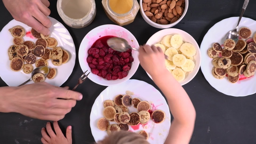 Top view family eating homemade breakfast. Tiny mini pancake cereal, sweet spreads, nuts, honey and fresh raspberries. Parents and child eat trendy quarantine food. Table with meal above. Royalty-Free Stock Footage #1053479576