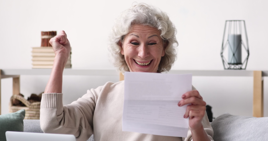 Head shot happy middle aged 70s retired woman holding paper letter, feeling excited by good news. Euphoric senior female client celebrating bank loan approve or last mortgage payment indoors. Royalty-Free Stock Footage #1053482405