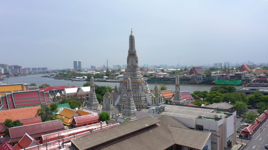 Aerial video of Wat Arun and Bangkok city skyline. Wat Arun is the old temple located near Chaophraya river in Bangkok of Thailand. | Shutterstock HD Video #1053486539