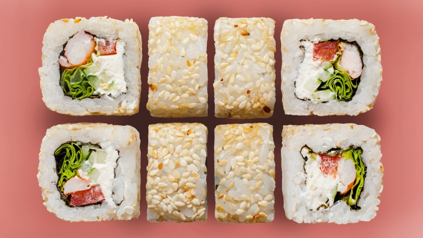 Stop motion video sushi rolls on colorful backgrounds. The menu of the online restaurant is a diverse sushi shot from above. Royalty-Free Stock Footage #1053486839