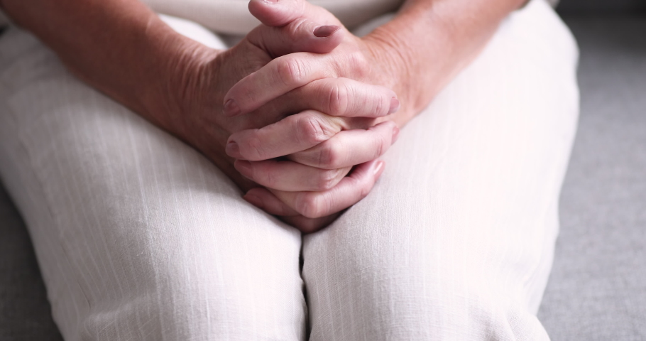 Close up middle aged mature woman clasped hands together, feeling nervous indoors, waiting for health test results. Old retired lady suffering from depression or loneliness, solitude anxiety concept.