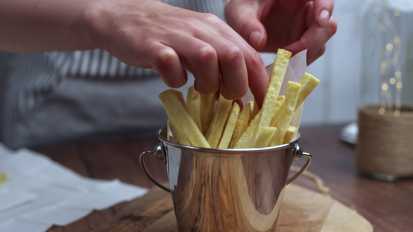 Placing a pile of waged potatoes in a sterling steel bowl. Concept of preparing French fries step by step. | Shutterstock HD Video #1053491858
