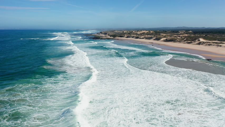 BEACH Portugal Praia do Malhão - aerial shot of an empty lonely sandy beach at the Atlantic Ocean in the soft morning light, flying low over the breaking waves along the beach