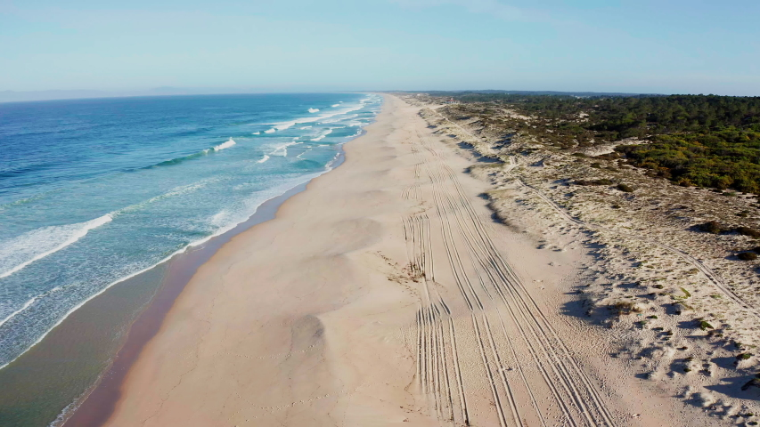 BEACH Portugal Praia do Pego - aerial shot of an empty lonely sandy beach at the Atlantic Ocean in the soft morning light – drone is flying high over tracks on the beach further out to the ocean Royalty-Free Stock Footage #1053493301