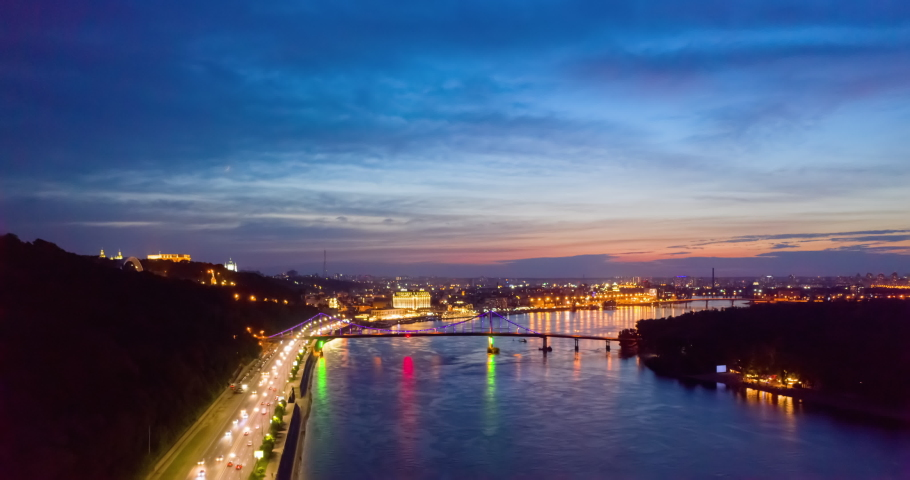 4K UHD Hyperlapse time-lapse of car traffic and people crossing road at night in in Kyiv. colorful led bridge across river and quay road