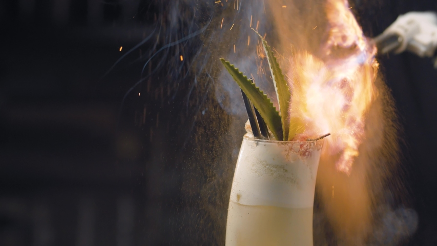 Close up bartenders hands sprinkling with burning cinnamon pina colada cocktail. Glass rotating on the background of the fire. Bar drinks series. | Shutterstock HD Video #1053494903