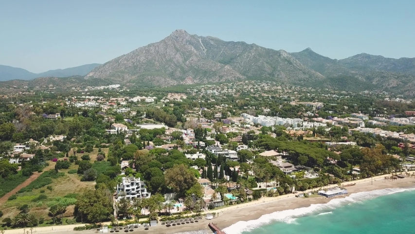 Sensational aerial view of luxury and exclusive area of Marbella, golden mile beach, view of Puente Romano Bridge and in Background famous La Concha mountain. Emerald water color Drone going backwards   Shutterstock HD Video #1053498659
