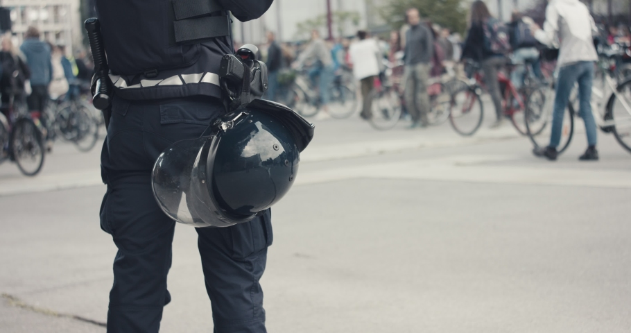 Police officer in full protection riot gear with helmet gun and baton guarding demonstrations on bicycles protest for protection of nature in Europe during pandemic