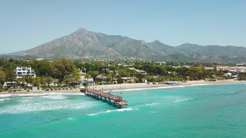 Beautiful and unique cinematic aerial view of luxury and exclusive area of Marbella, golden mile beach, Puente Romano Bridge.Luxury Clubs, Urbanisation in the most expensive area of Marbella. Forward Royalty-Free Stock Footage #1053499784