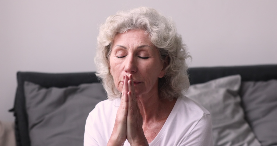 Head shot peaceful middle aged 60s grey haired woman folded hands in namaste, praying God for good luck. Faithful calm religious senior mature grandmother saying morning grace after waking up.