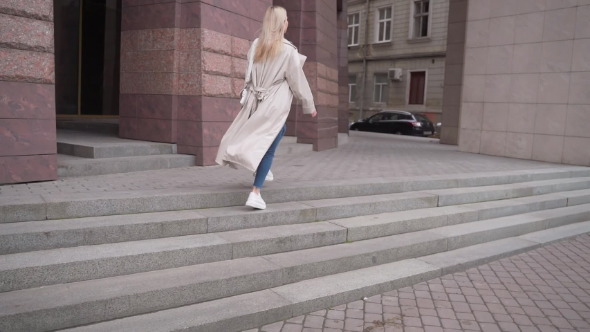 Young attractive blonde girl runs up the stairs to a meeting. rear and side view. slow motion. A woman in a coat or tench and jeans walks up the stairs in a hurry. does not have time.