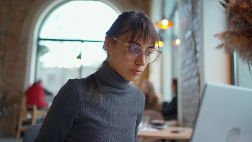 Portrait young woman in eyeglasses using laptop in coworking space or cafe and drinking coffee. female sitting in front open laptop computer. Study, learning, remote work, freelance. Royalty-Free Stock Footage #1053502670