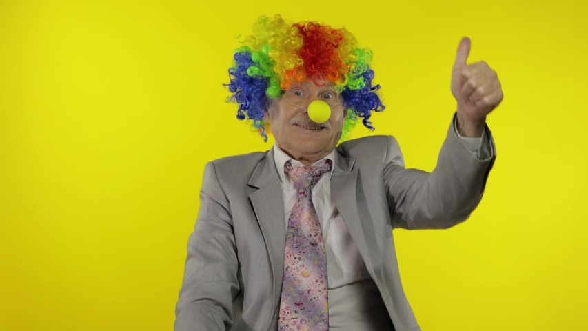 Senior clown director office worker in wig and business suit at work show thumb up. Guy businessman freelancer boss smiles, looks at camera. Expressions. Copy space. Halloween. Yellow background | Shutterstock HD Video #1053503621