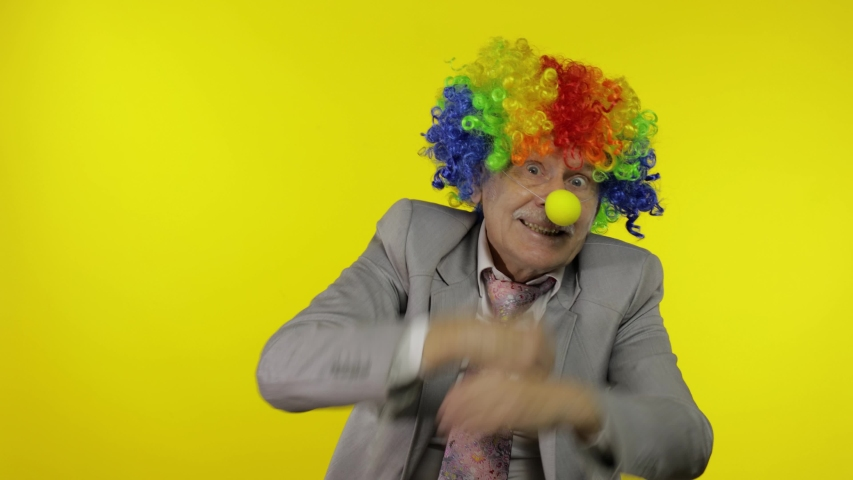 Senior clown manager office worker in wig and business suit at work dancing, entertains, celebrate victory, making silly faces. Guy businessman freelancer boss. Halloween. Yellow background | Shutterstock HD Video #1053503636
