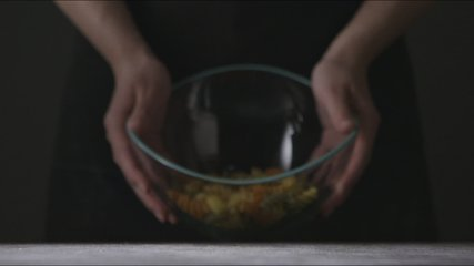 Raw italian pasta Fusilli Spirale colorful pours from glass bowl in a girls's hands on a dark wooden background. Slow motion, Full HD video, 240fps, 1080p. Close up view.