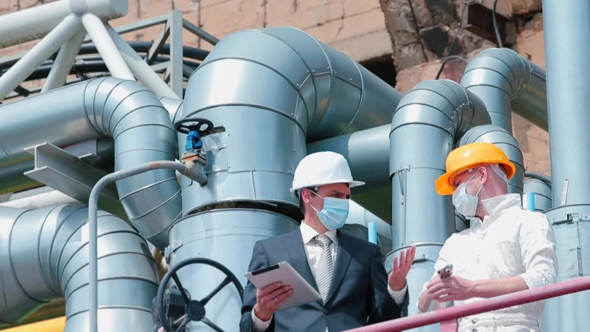 Manager and worker in protective masks face. Organization work in industrial sector during quarantine. Conflict of manager and worker on gas and oil production platform. Factory technical pipes. Royalty-Free Stock Footage #1053505007