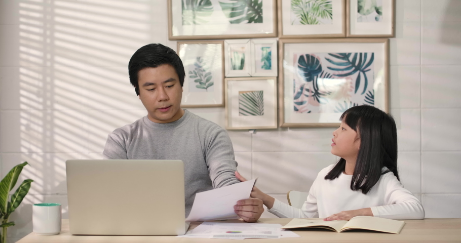 Upset daughter looking at working father, Busy asian business man speaking looking at laptop computer communicating by video call at home ignoring loving daughter. lack of family communication concept   Shutterstock HD Video #1053506360