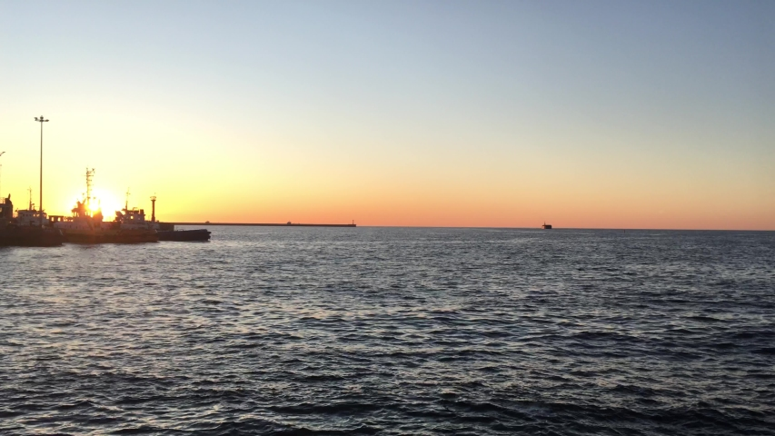 Sunset in the seaport tugs on the Sea