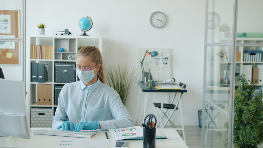 Man and woman office workers are working with charts and computers wearing masks and gloves during pandemic of covid-19. People and job concept. Royalty-Free Stock Footage #1053509132
