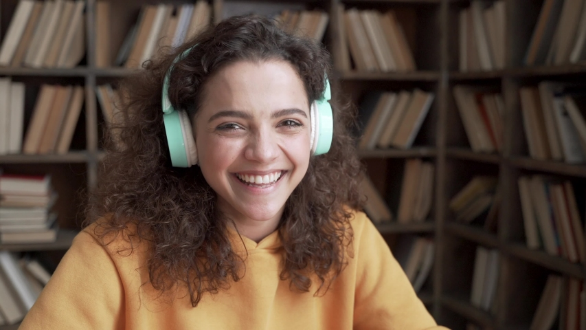 Happy positive latin teenage girl laughing at funny joke looking at camera in library. Cheerful hispanic teen school college student wear headphones having fun, smiling ethnic face close up portrait. Royalty-Free Stock Footage #1053511181